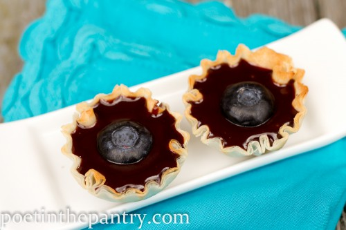 Mini phyllo dough tart shells filled with chocolate sauce, with a blueberry on top